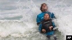 Monique Oliveira dibantu oleh relawan AdaptSurf berselancar di pantai Barra da Tijuca di Rio de Janeiro, Brazil. (AP/Felipe Dana)