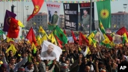 FILE - Masked people in guerrilla outfits hold up a poster of of jailed Kurdish rebel leader Abdullah Ocalan as they demonstrate during the Nowruz celebrations in southeastern Turkish city of Diyarbakir, Turkey, March 21, 2014.