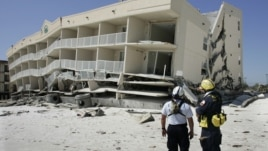 Members of the Federal Emergency and Management Agency's search and rescue team, Task Force 1 from Texas, plan their search of the Winfield Resort condominium September 17, 2004 after Hurricane Ivan struck the area in Orange Beach, Alabama.