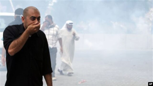 An anti-government protester reacts to clouds of tear gas fired by police in Manama, Bahrain, March 13, 2011