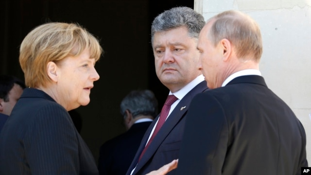 German Chancellor Angela Merkel, left, Russian President Vladimir Putin, right, and Ukrainian president-elect Petro Poroshenko, center, talk after a group photo in NOrmandy, France, June 6, 2014.