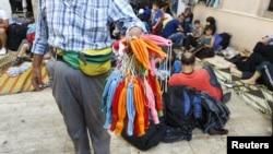 Cep telefonları su geçirmesin diye mültecilere balon satan bir sokak satıcısı
