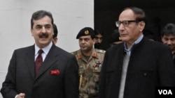 Perdana Menteri Pakistan Yousuf Raza Gilani dari Partai Rakyat Pakistan (kiri) berjalan dengan Presiden Partai Liga Muslim Pakistan Chaudhry Shujaat Hussain (kanan) di Lahore.