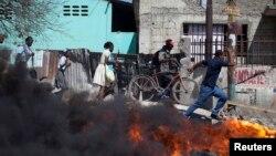 Wargamelewati barikade yang dibakar dalam protes-protes di Croix des Bouquets di pinggiran kota Port-au-Prince, Hairi (2/2). (Reuters/Andres Martinez Casares)