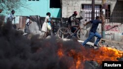 People pass a burning barricade during protests in Croix des Bouquets on the outskirts of Port-au-Prince, Feb. 2, 2015.