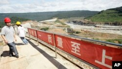 A Chinese engineer, left, walks by a fence with Chinese slogans reading: Safety first, highest quality and quantity near an entrance of a dam construction site by China National Heavy Machinery Corporation on the Tatay River in Koh Kong province, file photo.