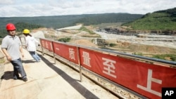 In this Oct. 6, 2012 photo, a Chinese engineer, left, walks by a fence with Chinese slogans reading: Safety first, highest quality and quantity near an entrance of a dam construction site by China National Heavy Machinery Corporation on the Tatay River in Koh Kong province, some 210 kilometers (130 miles) west of Phnom Penh.