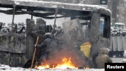 Pro-European protesters take cover behind a burnt bus during clashes with riot police in Kyiv, Jan. 22, 2014.