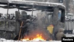 支持融入欧盟的乌克兰抗议者在基辅与防暴警察冲突时躲在一辆燃烧的巴士后面。(2014年1月22日)