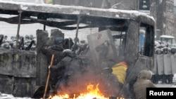 معترضان حامی اتحادیه اروپا پشت یک اتوبوس سوخته سنگر گرفتند - ۲۲ ژانویه ۲۰۱۴
