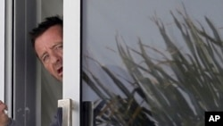 Phil Rudd, drummer for the rock band AC/DC, gestures from a window at his house in Tauranga, New Zealand, Nov. 6, 2014.