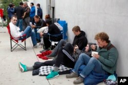 People wait in line after spending the night for the new Apple watch at Maxfield, a high-end fashion boutique in Los Angeles, April 24, 2015.