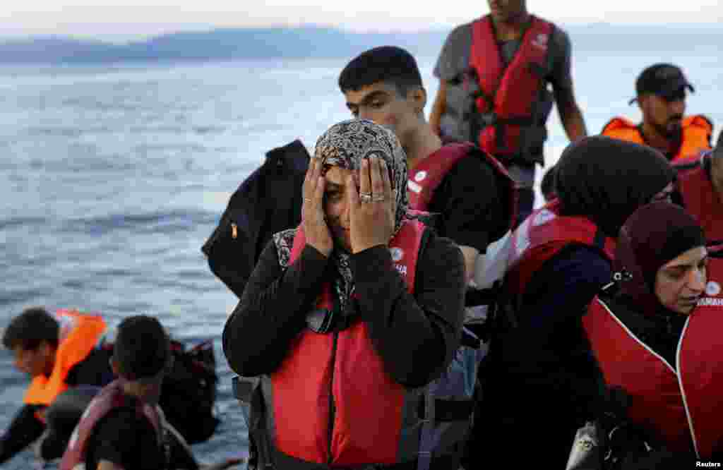 A Syrian refugee woman reacts while traveling in an overcrowded dinghy as it arrives at a beach on the Greek island of Lesbos, after crossing part of the Aegean Sea from Turkey.
