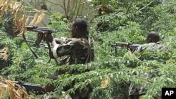Somali government soldiers in the bush take position during clashes between insurgents and Somali government soldiers with AU peacekeeping forces in southern Mogadishu's Bakara market neighborhood, May 22, 2011.
