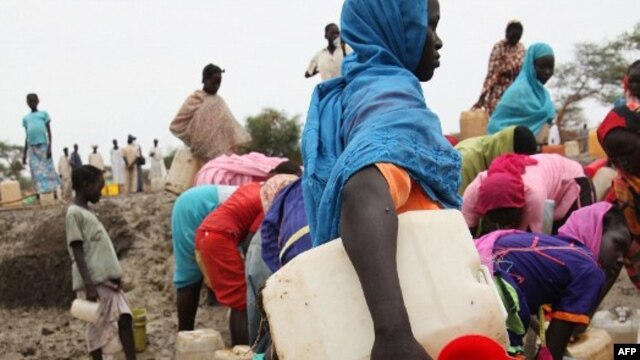 At the Jamam refugee camp, shows people gathering water at a man-made water hole, in South Sudan's Upper Nile state, where over 100,000 refugees have fled conflict in Sudan's Blue Nile state since September, June 15, 2012.