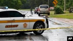 Автомобиль офиса шерифа Линкольн Каунти и полицейская лента блокируют улицу вокруг места убийства. Город Брукхэвен, Миссиссиппи. 28 мая 2017 г.
