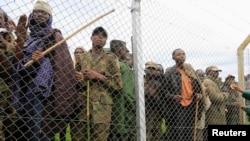 刚果M23叛军的战士(在铁丝网后)11月8日在向乌干达政府投降后在乌干达的一个村庄