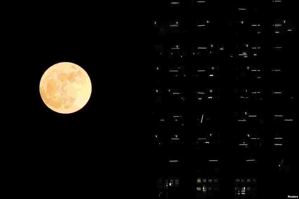 The supermoon is seen behind a building under construction in Hong Kong.