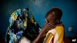Une victime des viols collectifs de Fizi, en février 2011, réconforte son fils