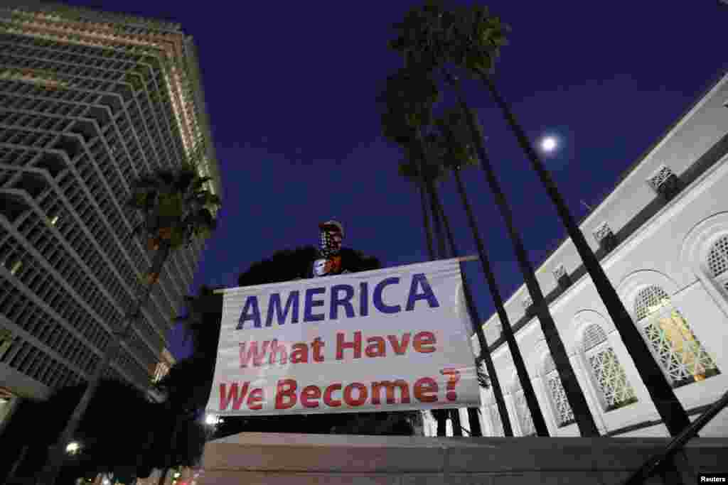 "A man holds a sign reading ""AMERICA What Have We Become?"" during a protest against the impeachment acquittal of U.S. President Donald Trump outside city hall in Los Angeles, California, Feb. 5, 2020."