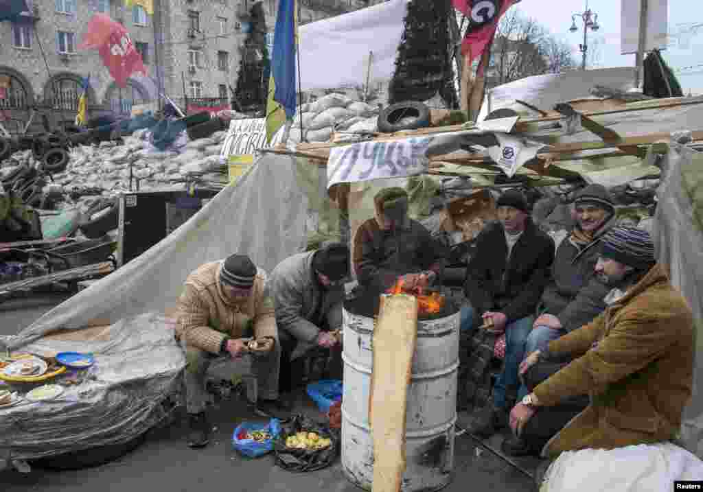 Ukrainian pro-EU demonstrators warm themselves by a fire during a rally in Independence Square, Kyiv, Ukraine, Dec. 20, 2013.
