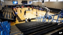 Yeshiva University players, foreground, warm up in a mostly empty Goldfarb Gymnasium at Johns Hopkins University before playing against Worcester Polytechnic Institute in a first-round game at the men's Division III NCAA college basketball tournament, Fri