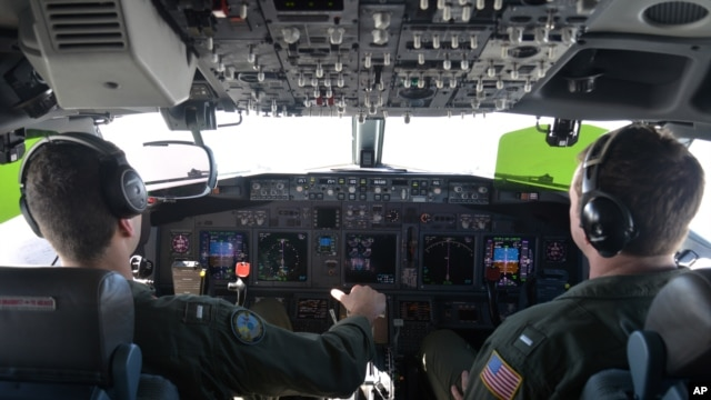 FILE - Lt. j.g. Kyle Atakturk, left, and Lt. j.g. Nicholas Horton, pilot a U.S. Navy P-8A Poseidon during a mission to assist in search and rescue operations for Malaysia Airlines flight MH370, March 19, 2014.
