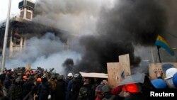 Para demonstran anti-pemerintah di Alun-Alun Kemerdekaan dekat gedung serikat perdagangan yang terbakar di pusat kota Kyiv (19/2). (Reuters/David Mdzinarishvili)