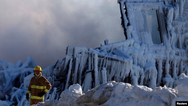 A firefighter looks on at the seniors residence Residence du Havre after a fire in L'Isle Verte, Quebec, January 23, 2014. (Reuters)