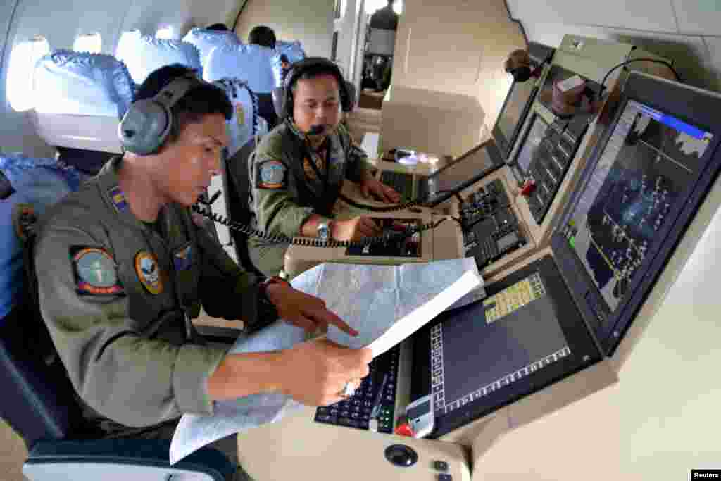Two members of the Indonesian Navy's Tactical Commanding Operator (TACCO) help with the search for AirAsia flight QZ 8501 on board a CN235 aircraft over Karimun Java, in the Java Sea, Dec. 28, 2014 in this photo taken by Antara Foto.