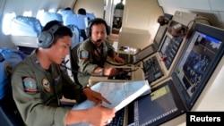Dua anggota TACCO TNI AL membantu pencarian pesawat AirAsia QZ 8501 yang hilang menggunakan pesawat CN235 di atas Karimun Jawa, di Laut Jawa, 28 Desember 2014 di foto yang diambil oleh Antara Foto.