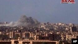 De la fumée et des débris après le bombardement de la ville de Deir el-Zour par le gouvernement syrien lors d'une bataille contre les militants de l'Etat islamique en Syrie, d'image d'une vidéo publiée le 2 novembre 2017 par l'agence de presse officielle syrienne SANA.