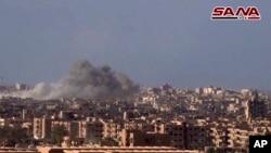 Foto yang diambil dari gambar video yang dirilis kantor berita SANA pada 2 November 2017 menunjukkan asap dan puing-puing setelah pemerintah Suriah menembaki Kota Deir al-Zor dalam serangan melawan militan ISIS.