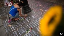 Một phụ nữ viết một thông điệp trên mặt đất để tưởng nhớ nạn nhân cuộc tấn công khủng bố tại Barcelona, Tây Ban Nha ngày 23/8/2017.