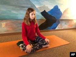 Aeva Schifferli, 12, menunjukkan latihan pernapasan yang menghilangkan stres di studio yoga ibunya di East Aurora, NY, 14 Mei 2019. (Foto: AP)