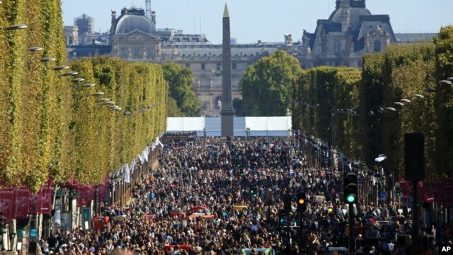 """FILE - People walk on the Champs Elysees during the """"day without cars,"""" in Paris, Sept. 27, 2015."""