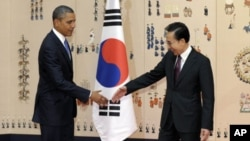 US President Barack Obama, left, shakes hands with South Korean President Lee Myung-bak at the Blue House, the official presidential house, in Seoul, South Korea, Sunday, March 25, 2012.