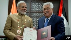 Palestinian President Mahmoud Abbas, right, decorates Indian Prime Minister Narendra Modi with the Grand Collar of the State of Palestine medal, during his visit to the Palestinian Authority headquarters in the West Bank city of Ramallah, Feb. 10, 2018.