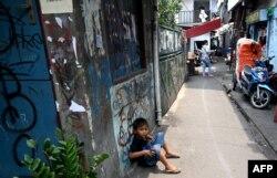 Seorang anak duduk di gang di sekitar rumahnya di Jakarta, 12 Oktober 2019. (Foto: AFP)