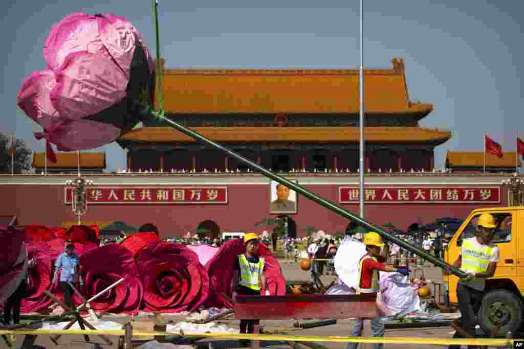 Workers guide an artificial flower blossom being lifted for a large floral display under construction in Tiananmen Square in Beijing.