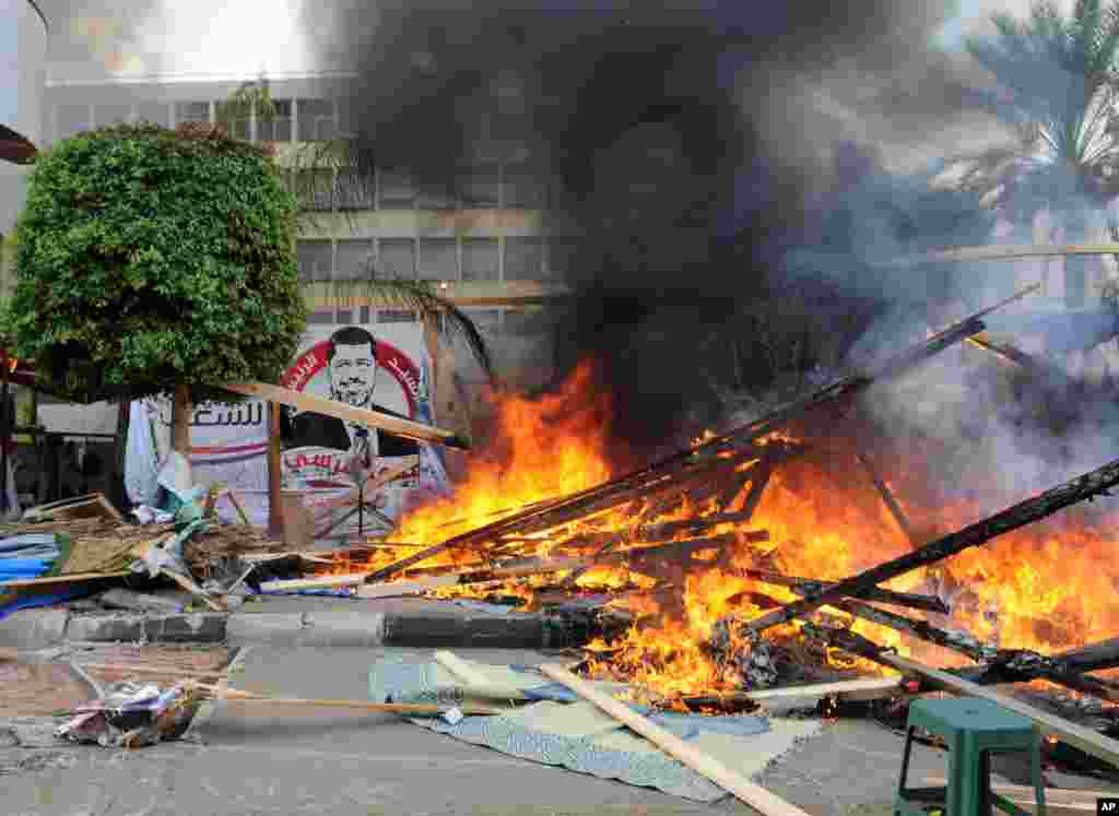 Makeshift wooden huts burn at a sit-in camp set up by supporters of ousted Islamist President Mohammed Morsi as Egyptian security forces clear the camp near Cairo University in Cairo's Giza district, Egypt, Wednesday, Aug. 14, 2013. Egyptian police in rio