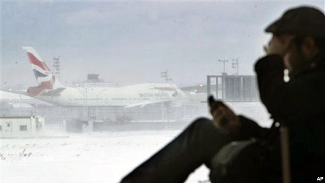 A passenger from San Francisco talks on his phone while a British Airways airplane sits motionless on the runway at John F. Kennedy International Airport in New York, 27 Dec 2010