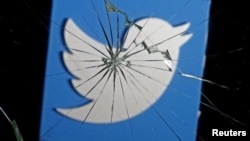 A 3D-printed Twitter logo is seen through broken glass, in this picture illustration taken Feb. 8, 2016.