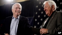 FILE - Sen. John McCain, R-Ariz., left, smiles as he gets a pat on the back from longtime friend and supporter Lt. Col. Orson Swindle, USMC Ret., Feb. 18, 2010, at a rally in Phoenix, Arizona.