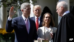 President Donald Trump watches as Supreme Court Justice Anthony Kennedy administers the judicial oath to Judge Neil Gorsuch during a re-enactment in the Rose Garden of the White House White House in Washington, April 10, 2017.