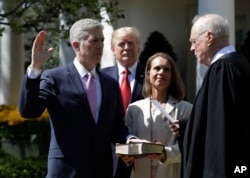 FILE - President Donald Trump watches as Supreme Court Justice Anthony Kennedy administers the judicial oath to Judge Neil Gorsuch during a re-enactment in the Rose Garden of the White House White House in Washington, April 10, 2017.