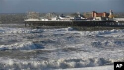 People walks along the shoreline as waves crash onto the beach in Brighton, England, Monday, Oct. 28, 2013. A major storm with hurricane force winds is lashing much of Britain, causing flooding and travel delays with the cancellation of many flights and