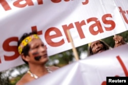FILE - Indigenous Indians protest in front of the Planalto Palace in Brasilia, Brazil, Nov. 26, 2014.