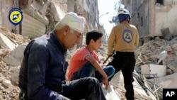 """在反政府武装占据的叙利亚东北城市阿勒颇,居民坐在断垣残壁中。(2016年10月11日档案照片,由被称为""""白钢盔""""的叙利亚民防队提供)"""