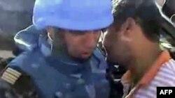 Кадр из видео, размещенного в Интернете в субботу. Согласно объясняениям автора, на нем изображены сирийцы общающиеся с наблюдателями ООН.